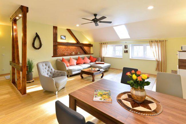 Wohnzimmer mit großer Wohnlandschaft und ein Sessel sowie ein großer Esstisch, bieten ausreichend Platz für bis zu vier Personen